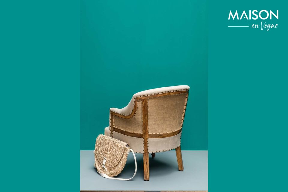 Fait de lin et de jute, ce confortable fauteuil repose sur des pieds façonnés en bois de manguier