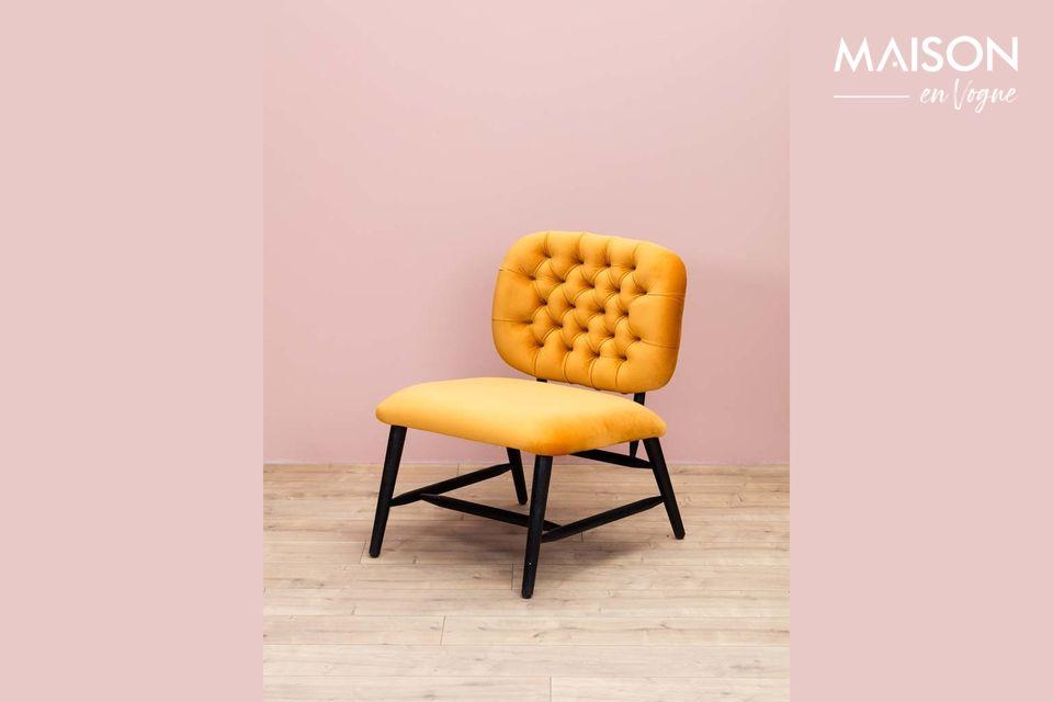 Un fauteuil d'aspect velours au dossier capitonné et de couleur ocre