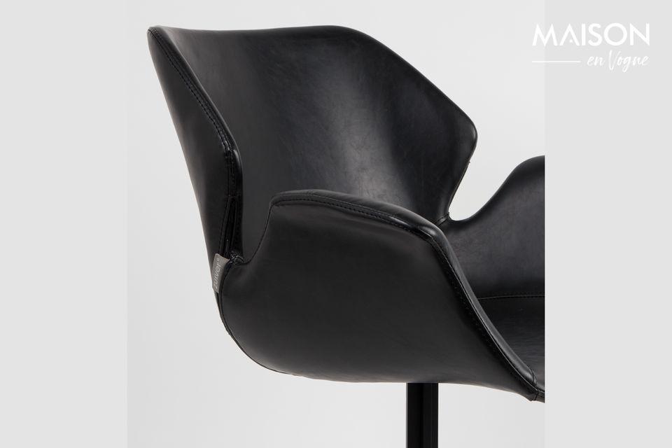 Elle héberge une assise noire, conçue en cuir, au design vintage