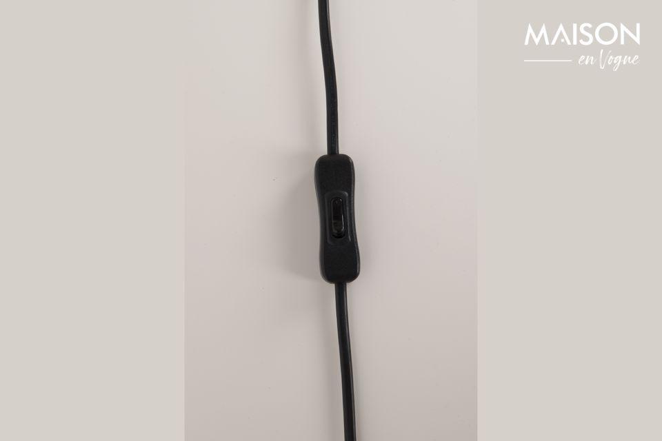 Stable et élégante, cette lampe de table est posée sur un trépied noir en fer peint