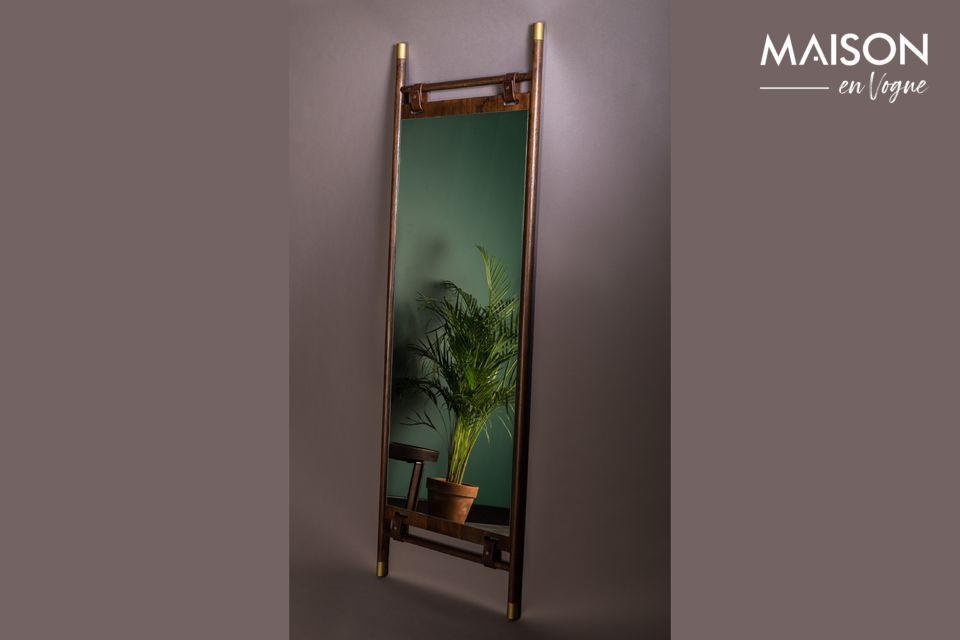 Le miroir flottant au centre du cadre est rattaché par des bracelets en cuir